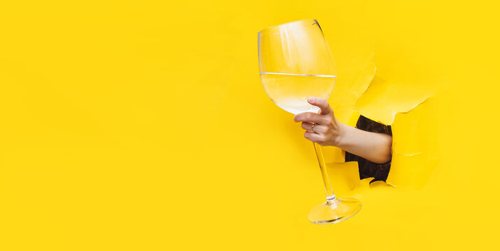 A left woman's hand emerges through a torn hole in yellow paper with a large glass with vermouth, water or vodka. The concept of alcoholism, drunkenness and hangover. Copy space.