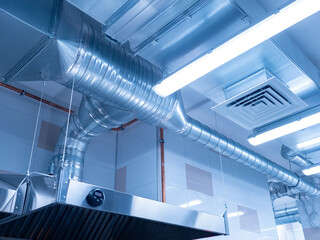 Fototapeta Ventilation system on ceiling of industrial room. Air purification system in restaurant. Pipes from the hood on ceiling, bottom view. Air purification system in an industrial kitchen. obraz