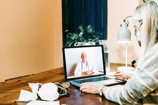 Senior woman on video call with doctor wearing protective face mask at home