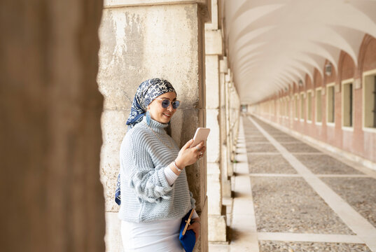 Young woman wearing headscarf using mobile phone while leaning on pillar
