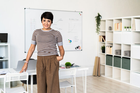 Portrait of businesswoman posing in office with hand in pocket