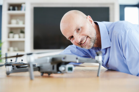 Smiling businessman examining quadcopter while standing at home