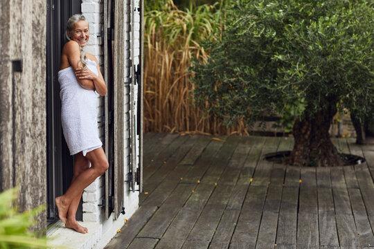 Happy mature woman wearing towel leaning on doorway of back yard