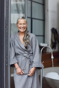 Smiling mature woman wearing bathrobe leaning by glass door in bathroom