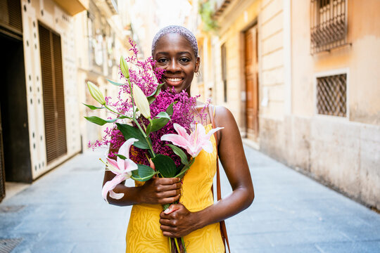 Happy woman in yellow dress holding flower bouquet while standing in city