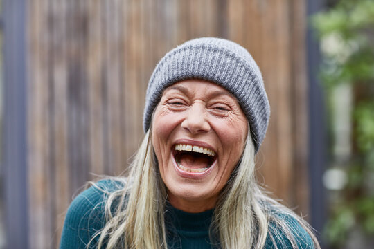 Laughing mature woman against house