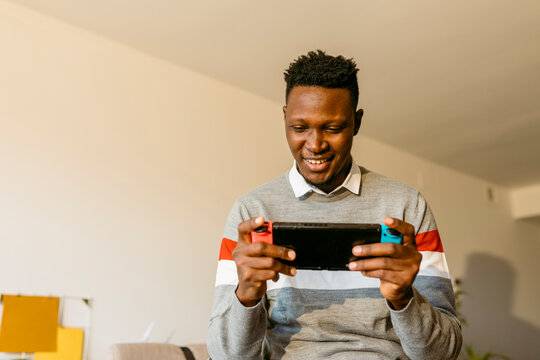Male entrepreneur playing video game at home during break from work