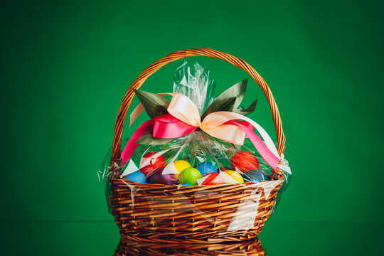 festive Easter basket with colorful eggs, green background