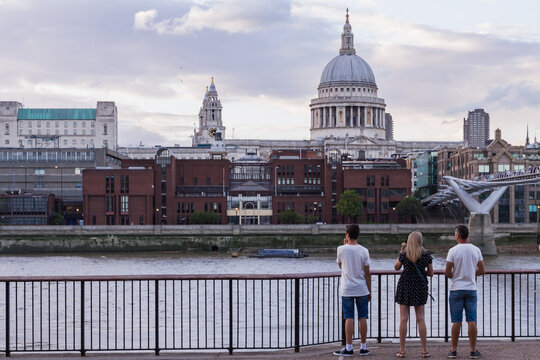 Tourists and friends in sharp focus looking at a defocus backdrop of St Paul's cathedral in central London from the south bank of the river Thames