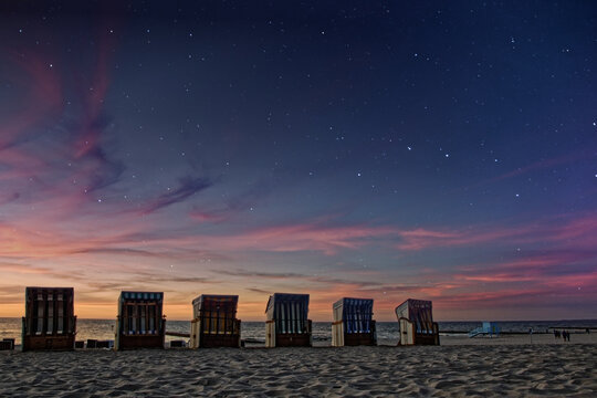Line of sun seats on the Baltic beach when the day meet night and stars appear