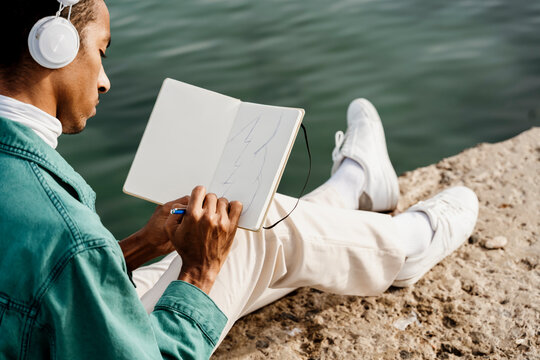 Young man drawing in book while sitting on pier by sea