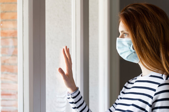 Redhead woman wearing protective face mask standing by window at home during COVID-19