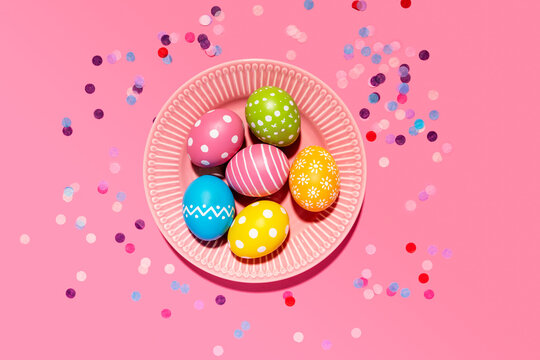 Colorful hand colored Easter eggs in tray with confetti on pink background