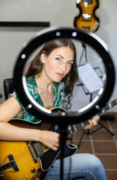 Confident woman with webcam light playing guitar while sitting at home