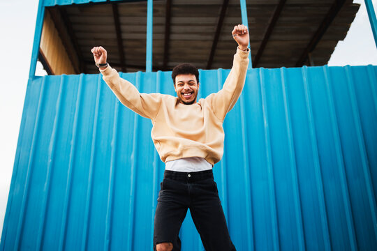 Cheerful man with hand raised jumping against blue wall