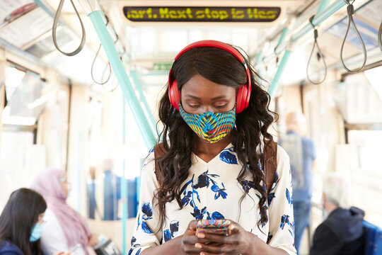 Businesswoman wearing face mask and headphone using mobile phone while standing in train