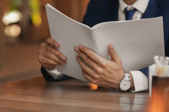 Young businessman reading magazine in cafe, closeup