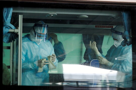 Medical workers get ready inside a bus before the expected arrival of a World Health Organisation (WHO) team in Wuhan