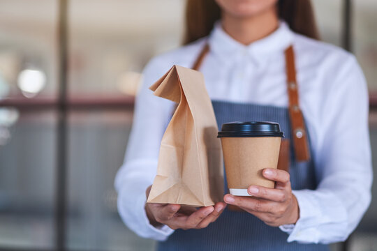 A waitress holding and serving paper cup of coffee and takeaway food in paper bag to customer in a shop