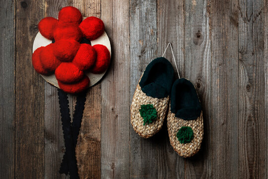 Black Forest Bollenhut and straw shoes in front of a wooden wall