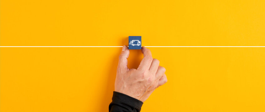 Male hand holds a blue wooden cube with logistics delivery truck icon on yellow background.