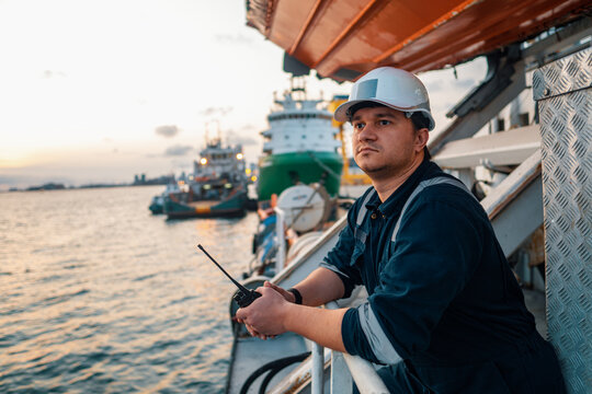 Marine Deck Officer or Chief mate on deck of offshore vessel or ship , wearing PPE personal protective equipment - helmet, coverall. Ship is on background