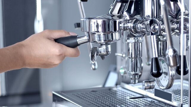 White woman's hand holding the handle and inserting a double porta filter in a shiny steel one group home manual espresso coffee machine. Side view high-quality photo jpg.