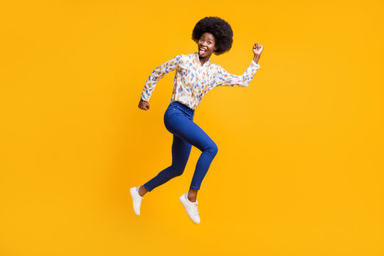 Full size profile side photo of brunette girl wear white print shirt blue pants jump run crazy isolated on yellow color background