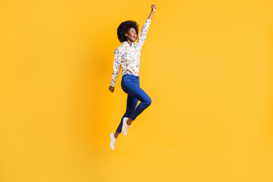 Full body photo of brown haired girl wear blue trousers white print shirt jump up hero isolated on yellow color background