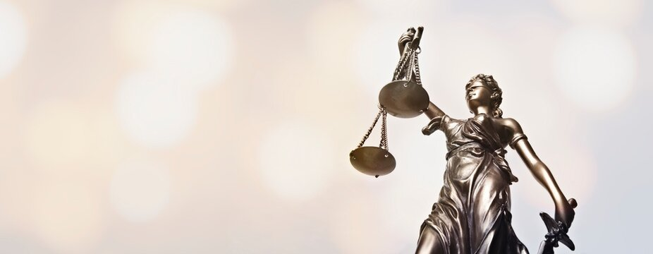 Lady justice - blindfolded figurine. Low angle view.  Panoamic image wih copy space.