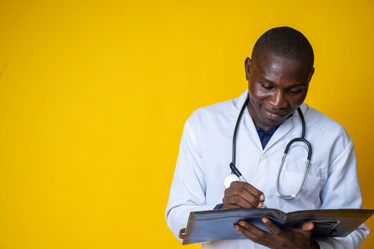 young handsome black medical doctor wearing his lab coat and hanging his stethoscope on his neck and taking note on a note pad
