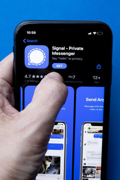 iPhone 11 on blue background with new messenger app Signal logo and icon displayed. Signal is a new application for messaging with high focus on privacy.