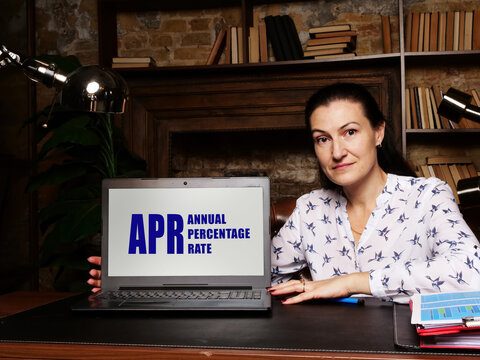 Businesswoman showing laptop with acronym  APR ANNUAL PERCENTAGE RATE on the screen