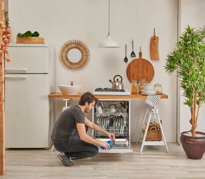 Man is filling liquid detergent in to the dishwasher, decorative little kitchen, sink and refrigerator.