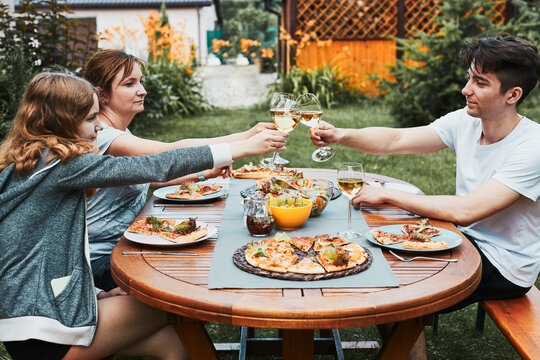 Friends making toast during summer picnic outdoor dinner in a home garden. Close up of people holding wine glasses with white wine over table with pizza, salads and fruits. Dinner in a orchard