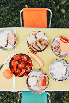 Breakfast prepared during summer vacation on camping. Bread, cottage cheese, cold meat, tomatoes, fruits and coffee cups on table. Close up of outdoor table setting set under tent