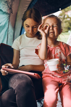 Two girls sisters spending family time in a tent on camping. Children using tablet playing games online during summer vacation