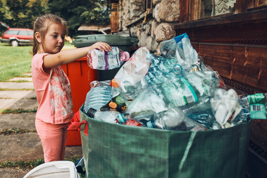 Child little girl throwing out plastic bottle to big container full of plastic waste