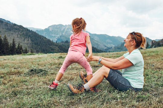 Little girl playing with her mother on grass enjoying summer day. Happy family playing in the field during vacation trip in mountains