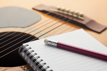 Close-up Of Note Pad And Pencil On Guitar