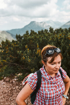 Woman with backpack hiking in a mountains, actively spending summer vacation, having break after going up on a hill standing on mountain path by mugo pine