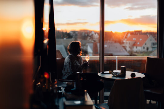 relaxed woman indoors enjoying a glass of wine and looking to the sunset trough a big window