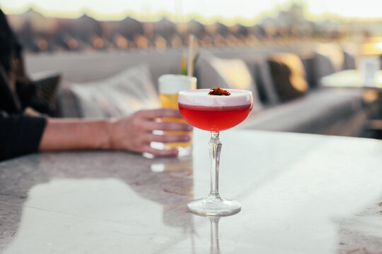 Red and yellow cocktails on a marble table. Sunny rooftop terrace, couches, pillows, relaxed atmosphere