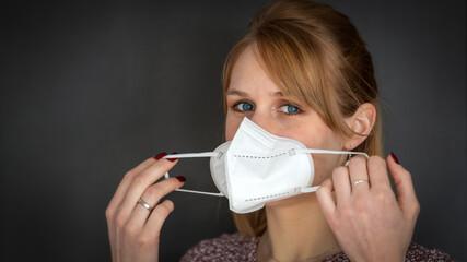 Junge rotblonde Frau zieht sich eine FFP2 Maske zum Schutz gegen das Coronavirus an - isoliert vor...