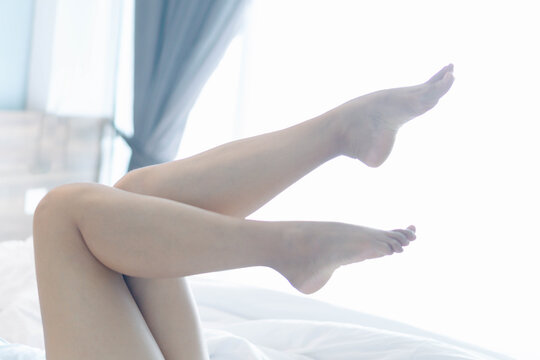 Closeup woman legs on white bed with over light form window, beauty and skin care concept, selective focus