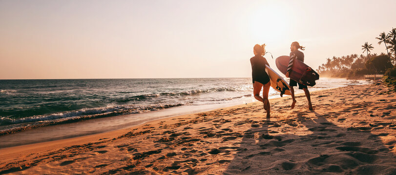 Young beautiful couple walking along the sandy beach near the ocean at sunset with surfboards, outdoor activities and sports holidays