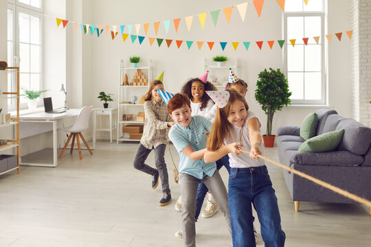 Team of happy smiling diverse children in funny cone hats playing tug-of-war in spacious decorated room at birthday party at home. Group of kids enjoying exciting games in after school club or center