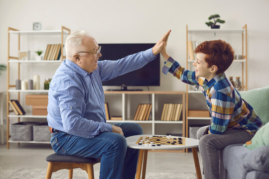 Well done. Good job. Senior man and little child smiling and high-fiving each other after playing checkers. Happy grandfather and grandson having fun and enjoying intellectual board games at home