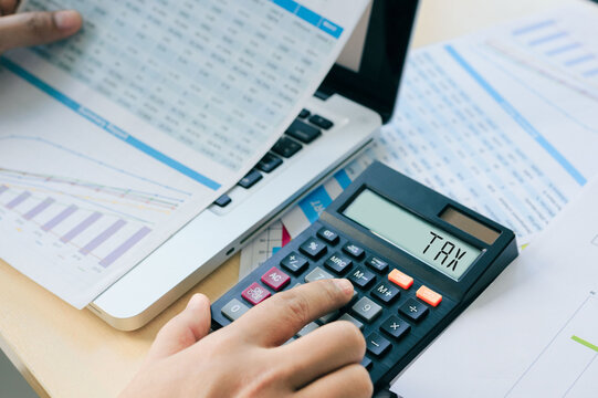 Close up Businessman and partner using calculator and laptop for calculating finance, tax, accounting, statistics, and analytic research concept. Tax word on a calculator. Business and tax concept.