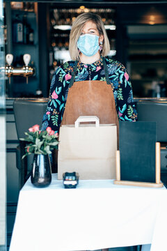 portrait of female worker at the pub restaurant standing the delivery table wearing protective face mask